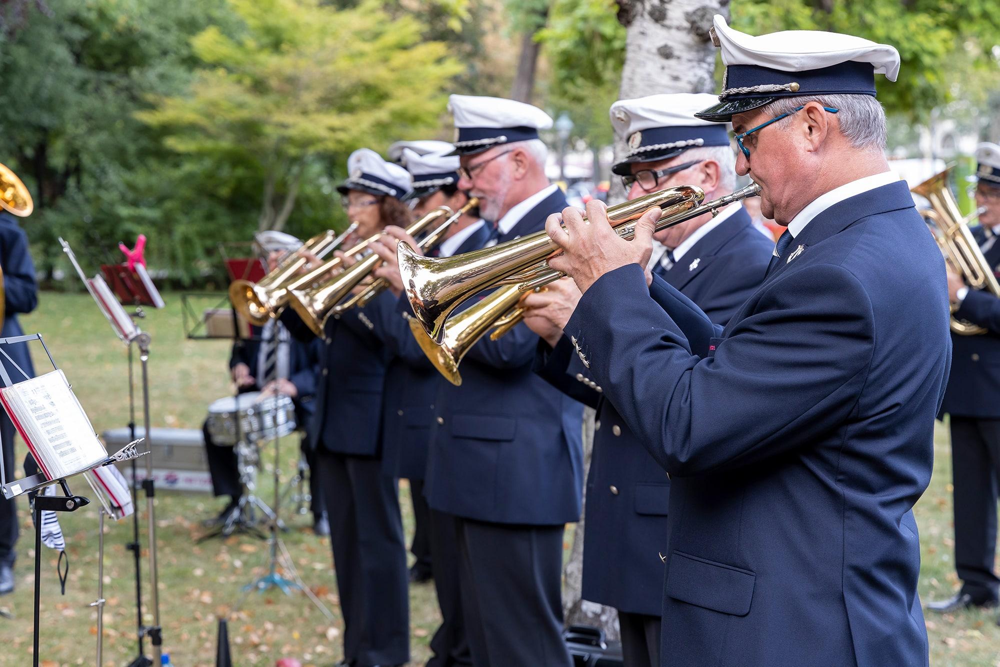 Blasmusiker der Wiener Netze spielen in Uniform Trompete im Park.