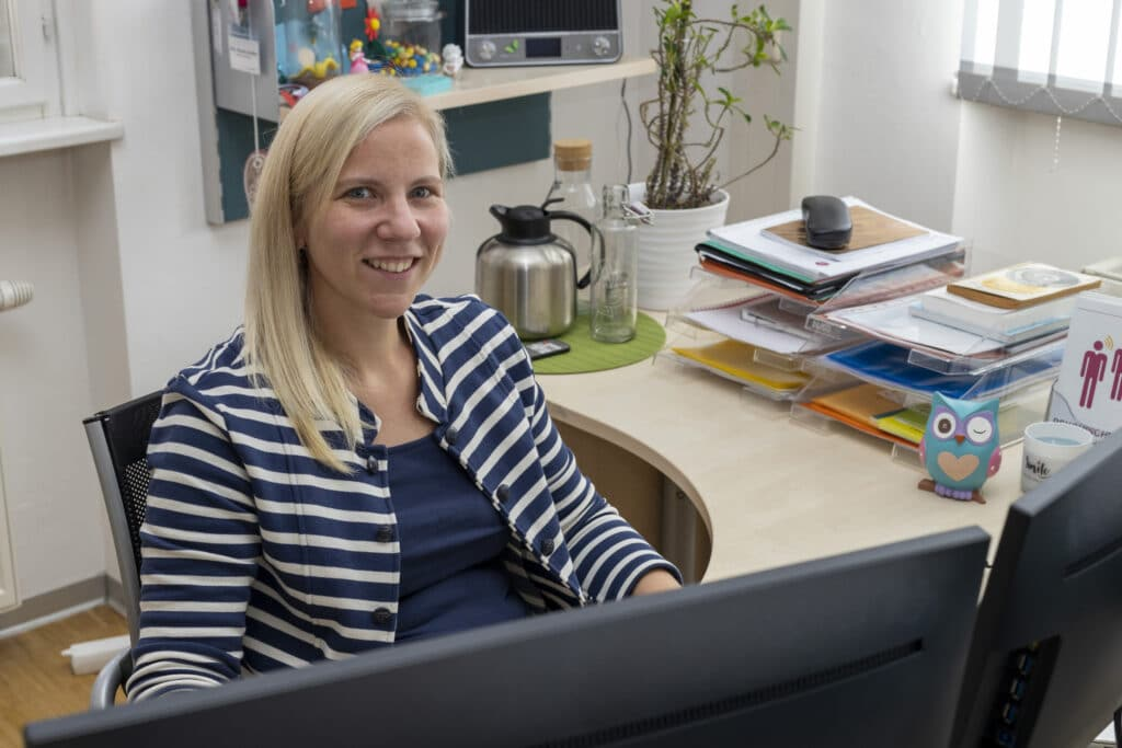Mitarbeiterin der Wiener Netze sitzt lächelnd vor Monitor.
