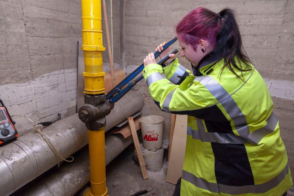 Wiener Netze Mitarbeiterin arbeitet am Gasrohr in einem Keller.