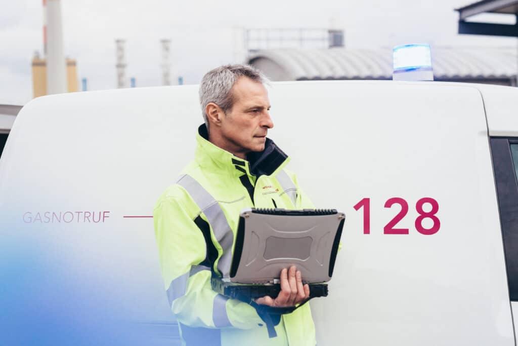 Mann mit portablen Monitor vor Fahrzeug des Störungsdienstes