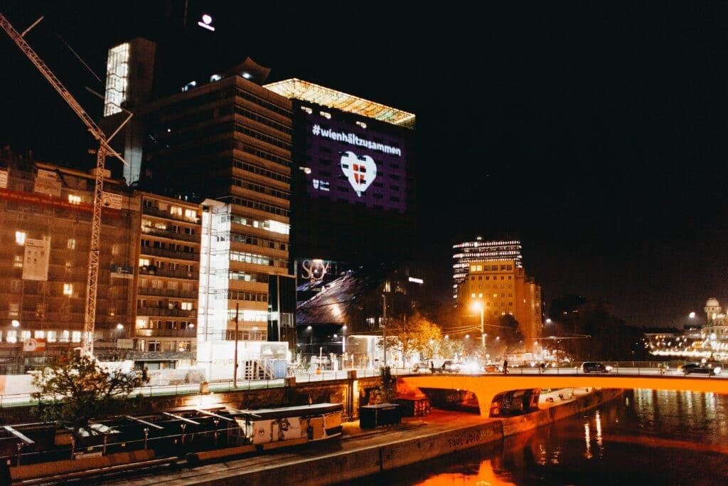 """Hochhaus bei Nacht mit Projektion """"Wien hält zusammen""""."""