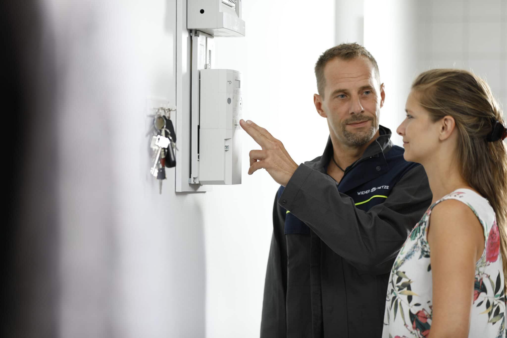 Mann und Frau stehen vor einem Smart Meter