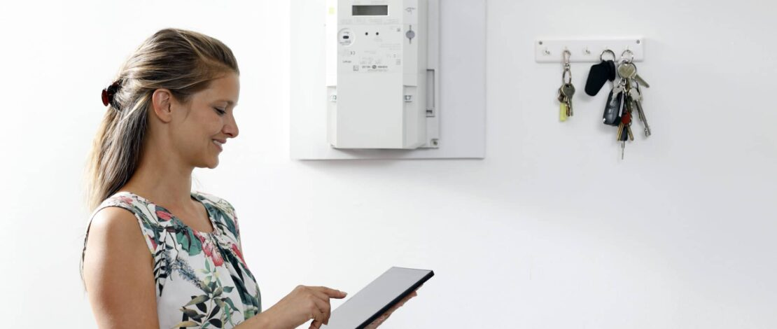 Frau mit Tablet in der Hand neben Smart Meter