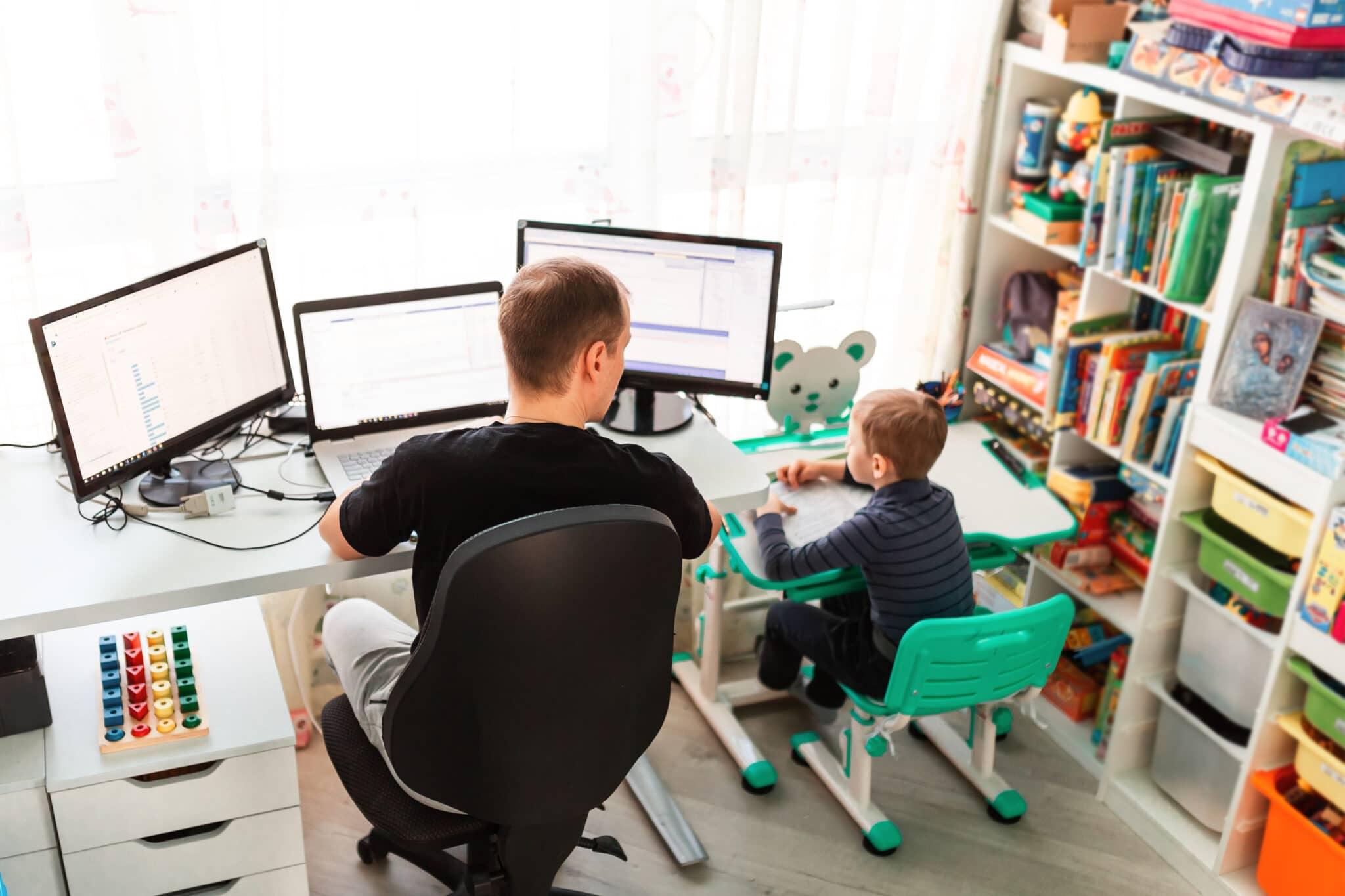 Mann arbeitet beim Computer; Kind sitzt daneben und zeichnet