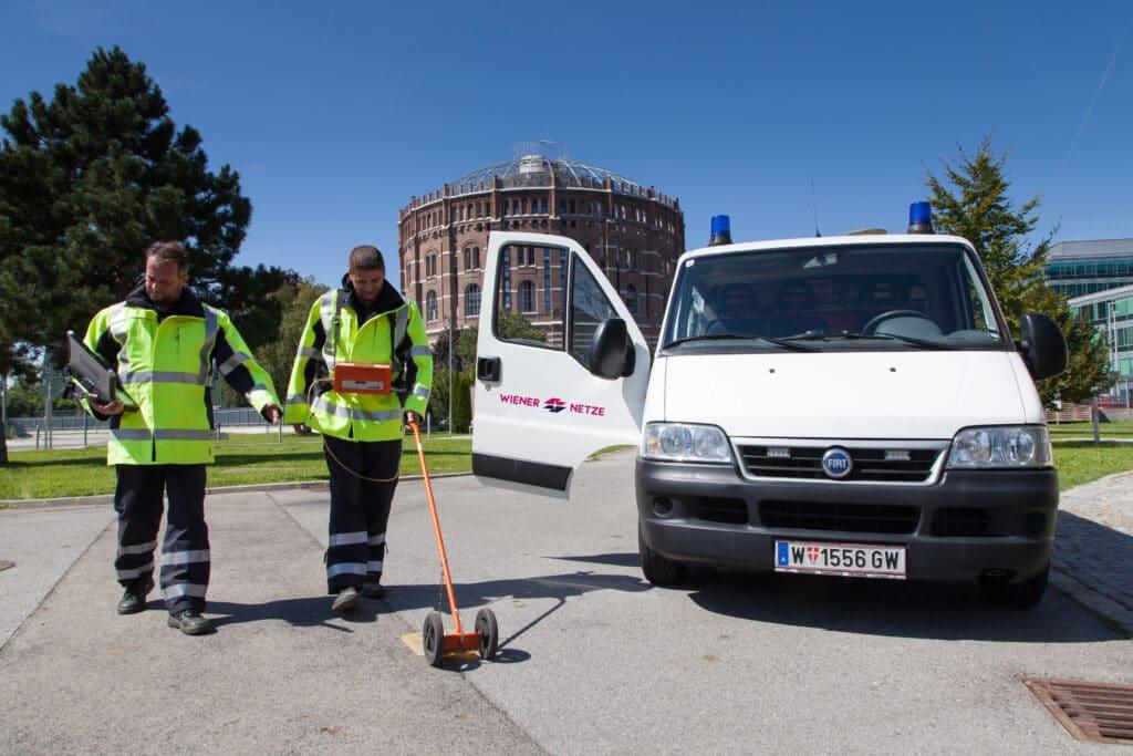 Zwei Männer in Arbeitskleidung spüren undichte Gasleitungen an einer Straße auf