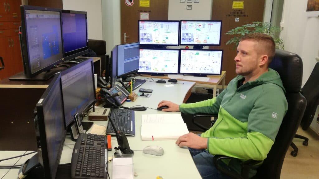 Mann sitzend vor mehreren Monitoren in Kommandozentrale
